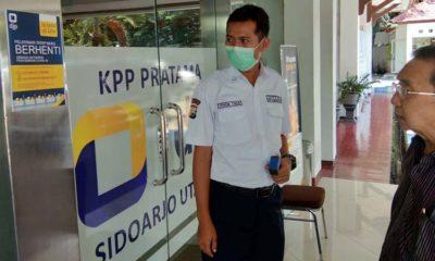 PEMERIKSAAN - Sejumlah petugas KPP Pratama Sidoarjo Utara menggunakan masker dan pengunjung diperiksa suhu badannya sebagai antisipasi penyebaran virus Corona beberapa hari lalu