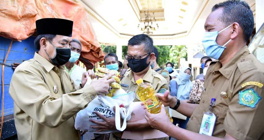 DISTRIBUSI - Wabup Sidoarjo, Nur Ahmad Syaifuddin memberangkatkan truk distribusi sembako bagi warga terdampak Covid-19 senilai Rp 40,5 miliar di Pendopo Delta Wibawa, Senin (20/04/2020). (wan)