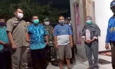 SEMBUH - Pemerintah Desa Jabaran, Kecamatan Balongbendo, Sidoarjo menyambut kedatangan Ny Riyayah (45) pasien Covid-19 sembuh didampingi petugas Polsek, Koramil dan keluarga, Minggu (17/05/2020) malam