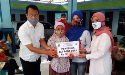 Pj. Kepala Desa Grinting, Kecamatan Tulangan Herawati secara simbolis menyerahkan BLT DD kepada warga. (par)