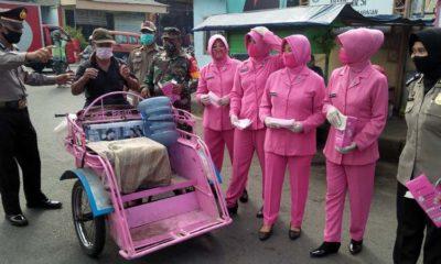 Anggota Bhayangkari Polsek Wonoayu memberikan masker kepada abang becak di jalan raya Jimbarankulon. (par)