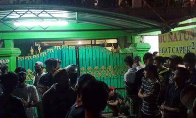 PENASARAN - Ratusan warga berkumpul di depan rumah korban Tin Kartini (70) pemilik rumah pijat Bu Natus di JL Brigjen Katamso No 170 Desa Kedungrejo, Kecamatan Waru, Sidoarjo, Jumat (24/7/2020) malam