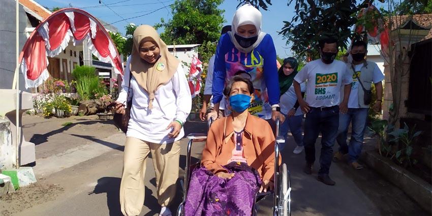 KURSI RODA - Istri Bacabup Bambang Haryo Soekartono (BHS), Ny Asrilia Kurniawati Bambang Haryo menyerahkan bantuan kursi roda kepada Ny Murti (55) warga Desa Jiken, Kecamatan Tulangan yang sudah 12 tahun mengalami kelumpuhan, Minggu (09/08/2020)
