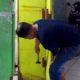 PERBAIKI - Korban pencurian Agus memperbaiki pintu di stan Warkop miliknya yang ada di Pasar Krian, Sidoarjo usai dibobol kawanan pencuri, Senin (10/08/2020)