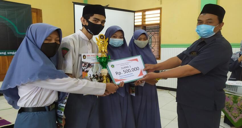 JUARA: Humas SMK YPM 8 Sarirogo Sidoarjo, Didik Teguh Wahyudi menyerahkan sejumlah hadiah kepada belasan siswa dan siswi berprestasi baik dalam skala kabupaten hingga tingkat nasional di UGM di aula sekolah, Senin (19/10/2020).